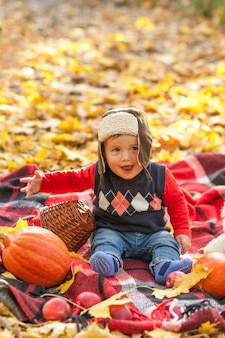 Glückliches baby mit der strickjacke, die auf einer decke sitzt