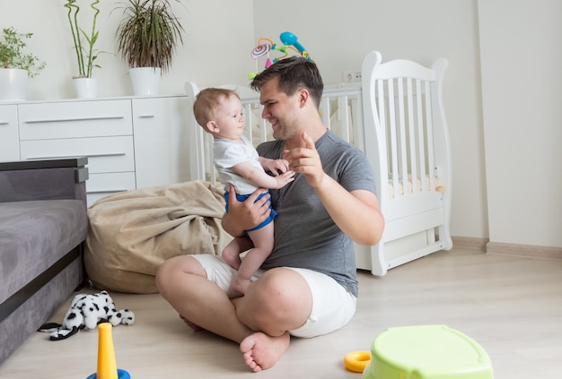 Glückliches baby und junger vater, die im wohnzimmer spielen
