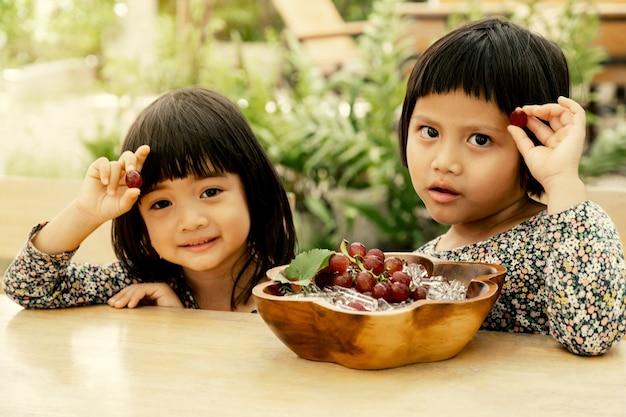Glückliches baby und kind, die zwillingskleidung tragen, sitzen auf dem tisch mit einem teller trauben, die in eis einfrieren