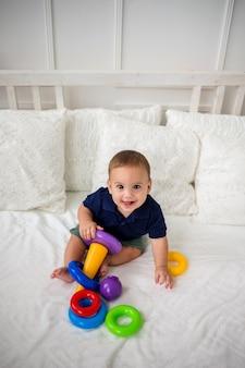 Glückliches baby und spielt mit einem pyramidenspielzeug. der blick von oben