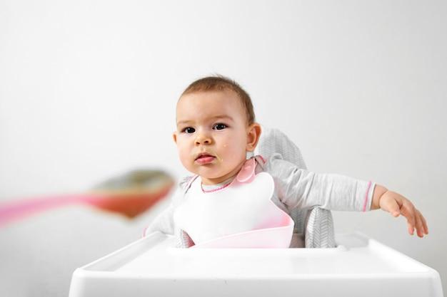 Glückliches babykleinkind im hochstuhl mit löffel in seiner hand
