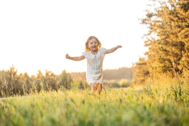 Glückliches babylächeln. kleines mädchen, das bei sonnenuntergang im freien läuft.