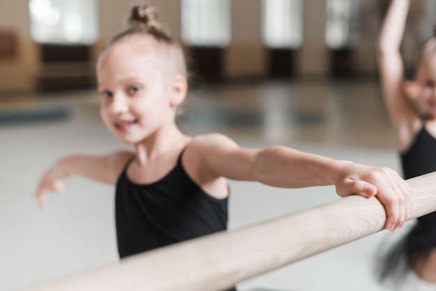 Glückliches ballerinamädchen, das auf hölzerner stange übt