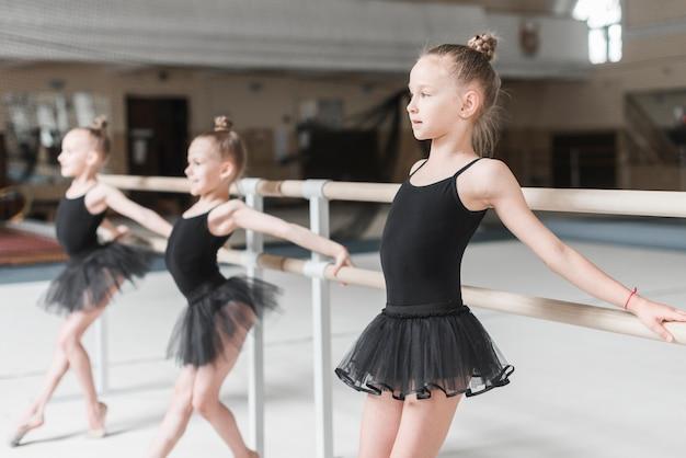 Glückliches ballerinamädchen, das bei barre mit ihren freunden übt
