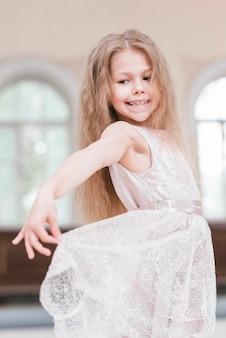 Glückliches ballerinamädchen mit dem langen haar, das ihr kleid hält