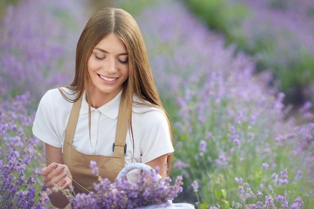 Glückliches bauernmädchen mit blumenkorb-lavendelfeld