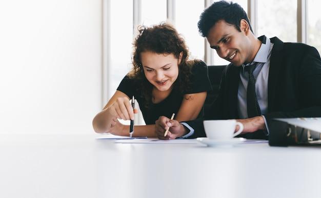 Glückliches besprechen des jungen geschäftsteams auf datenblättern auf schreibtisch während kleine sitzung