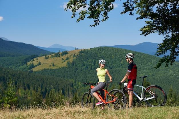 Glückliches bikerpaar, mann und frau, die mit fahrrädern auf grasbewachsenem hügel unter großem grünem ast stehen, lächeln und einander an sonnigem sommertag schauen.