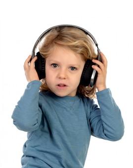 Glückliches blondes kind mit kopfhörern ein blaues t-shirt