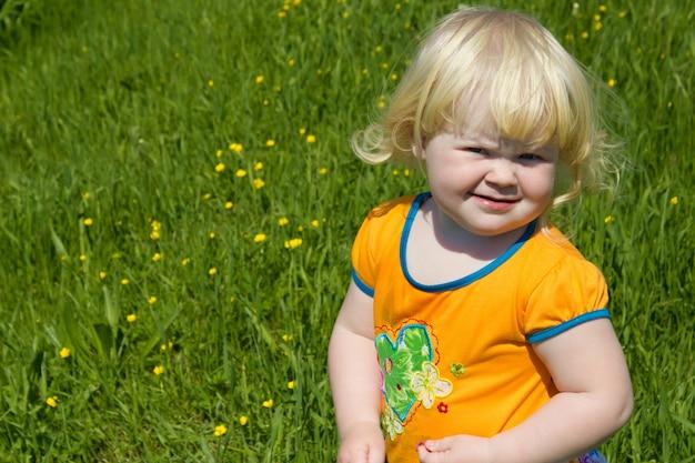 Glückliches blondes kleines mädchen im sommer, der spaß auf der natur hat