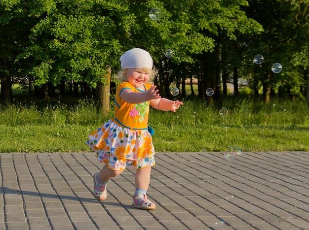 Glückliches blondes kleines mädchen im sommer, der spaß mit seifenblasen draußen hat