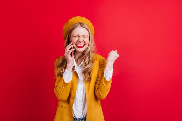 Glückliches blondes mädchen im barett, das mit lächeln am telefon spricht. aufgeregte französische frau lokalisiert auf roter wand.
