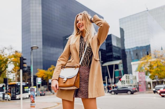Glückliches blondes mädchen im lässigen outfit des frühlings, das draußen geht und ferien in der großen modernen stadt genießt. trägt einen beige wollmantel und eine abgestreifte bluse. stilvolles zubehör.