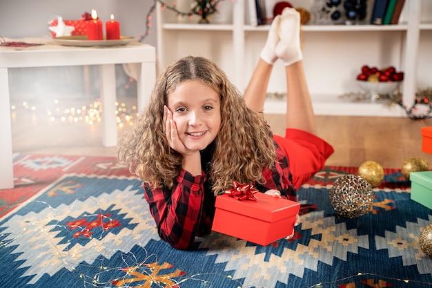Glückliches blondes mädchen mit weihnachtsgeschenkbox lächelnd auf einem teppich