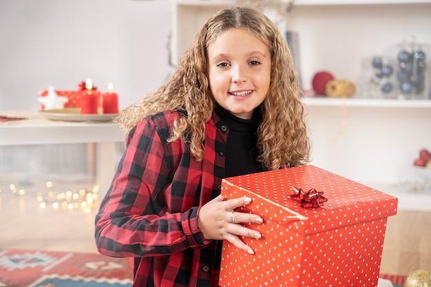 Glückliches blondes mädchen mit weihnachtsgeschenkbox