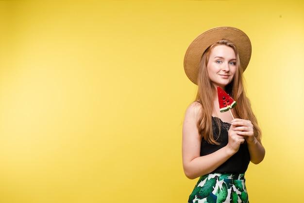 Glückliches blondes modell im hellen sommerblick, der süßigkeiten isst.
