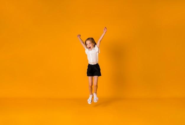 Glückliches blondes schulmädchen in uniform springt auf gelbem hintergrund mit einer kopie des raumes
