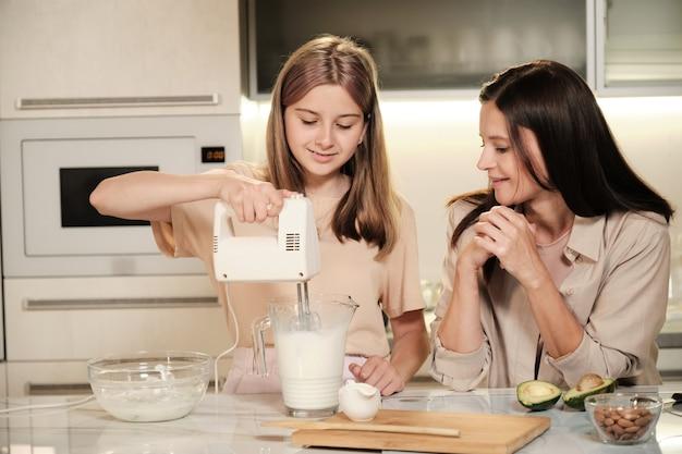 Glückliches blondes teenager-mädchen, das elektromixer oder mixer im großen glaskrug mit frischer milch und früchten hält, während mutter beim kochen hilft