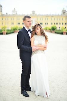 Glückliches brautpaar auf einem spaziergang in der alten europäischen stadtstraße wunderschöne braut im weißen hochzeitskleid zusammen mit einem hübschen bräutigam