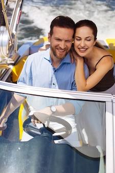 Glückliches brautpaar. charmantes junges paar, das ein boot segelt und glücklich lächelt, während es ihre fahrt genießt