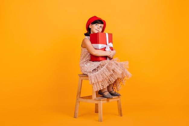 Glückliches brünettes kind, das auf stuhl mit geschenk sitzt. kleines geburtstagskind trägt süßes kleid.