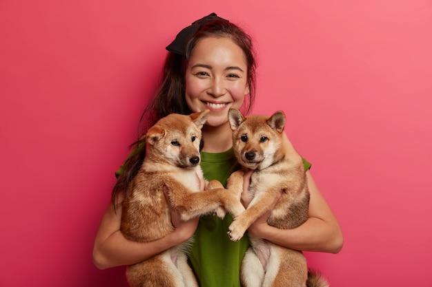 Glückliches brünettes mädchen adoptiert zwei welpen aus dem tierheim, glücklich, neue freunde zu haben, hält haustiere, ist hundeliebhaber, geht spazieren. tierhalter schlägt vor, haustier zu adoptieren, lächelt gerne und hat freundschaftliche beziehungen