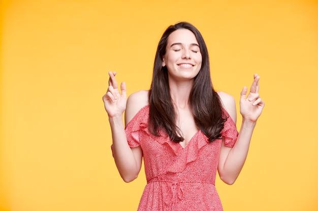 Glückliches brünettes mädchen im roten kleid, das ihre finger kreuzt und ihre augen geschlossen hält, während wunsch wünschend