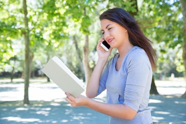 Glückliches buch junger dame leseund um telefon im park ersuchend