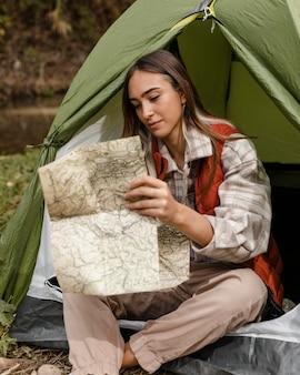 Glückliches campingmädchen im wald, das die karte prüft