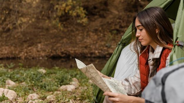 Glückliches campingmädchen im wald, das die kartenseitenansicht prüft