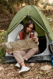 Glückliches campingmädchen im wald, das die kartenvorderansicht prüft