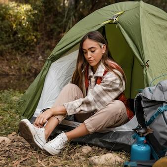 Glückliches campingmädchen im wald, das ihre schnürsenkel bindet