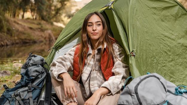 Glückliches campingmädchen im wald, das in der vorderansicht des zeltes sitzt