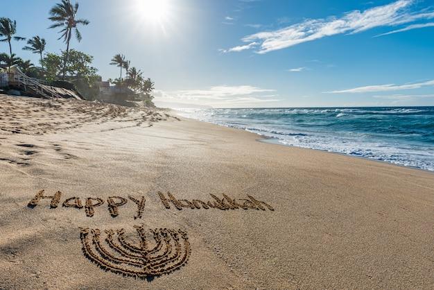 Glückliches chanukka geschrieben im sand mit einem chanukka mit einem tropischen strand und ozean
