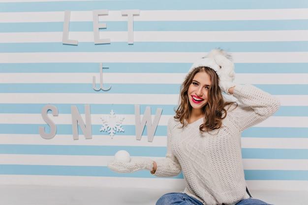 Glückliches, charmantes modell mit zarter haut und entzückendem lächeln, das in winterkleidung niedlich posiert und gegen wand mit schöner inschrift sitzt
