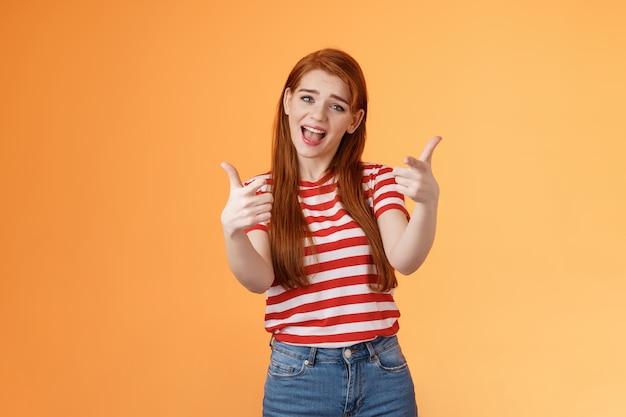 Glückliches cooles rothaariges freches mädchen singt mit der zeigekamera, das über dich spricht, gratuliere freund zu guter arbeit...