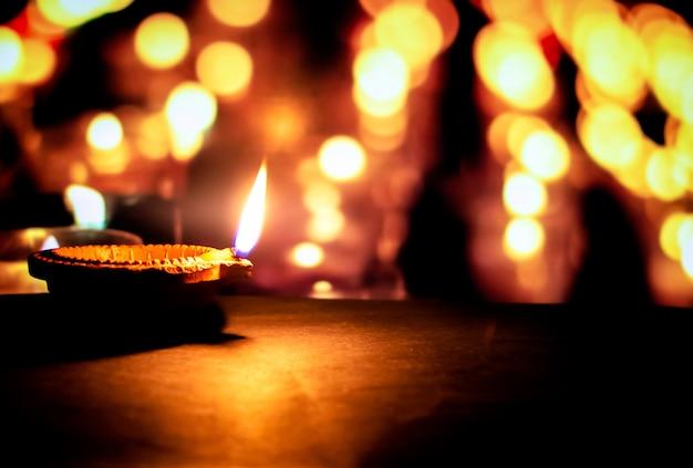Glückliches diwali. ton-diya-kerze beleuchtet in dipavali, hinduistisches lichterfest. traditionelle öllampe auf dunklem hintergrund