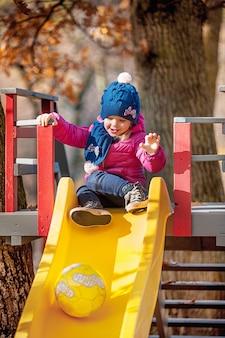Glückliches dreijähriges baby in der jacke auf rutsche