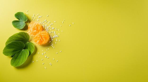 Glückliches dussehra-konzept. grünes blatt und reis auf gelbem pastellhintergrund