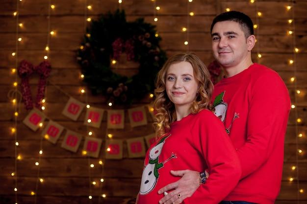 Glückliches ehepaar, das neben weihnachtsbaum bindet
