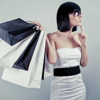 Glückliches einkaufsmädchen, das taschen hält