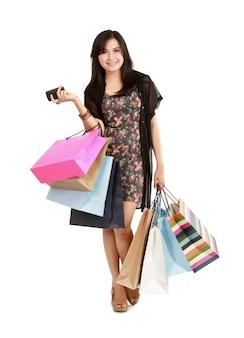 Glückliches einkaufsmädchen mit dem telefon. auf weißem hintergrund isoliert