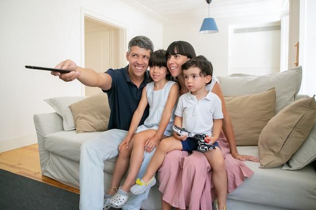 Glückliches elternpaar mit zwei kindern, die fernsehen, auf der couch im wohnzimmer sitzen und fernbedienung verwenden.