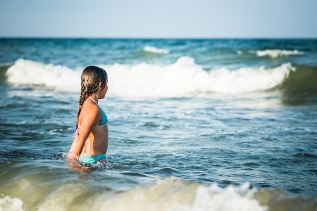 Glückliches emotionales kleines mädchen badet in den schaumigen stürmischen meereswellen an einem sonnigen warmen sommertag