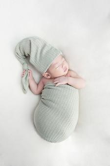 Glückliches entzückendes baby, das in der krippe schläft. kleinkind, das tageshaar im elternbett hat