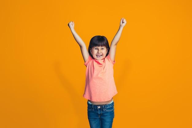 Glückliches erfolgreiches jugendlich mädchen, das feiert, ein gewinner zu sein. dynamisches energetisches bild des weiblichen modells