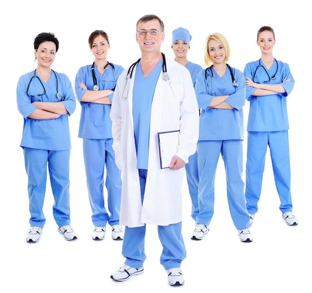 Glückliches erfolgreiches kommando der chirurgen mit einem reifen arzt im vordergrund
