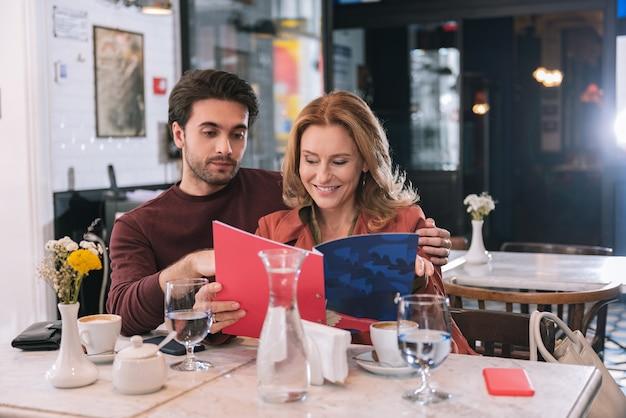 Glückliches erfolgreiches paar, das menü liest und am tisch aufwirft