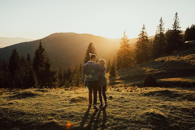 Glückliches erstaunliches paar, das bei sonnenuntergang mit erstaunlichem bergblick umarmt.