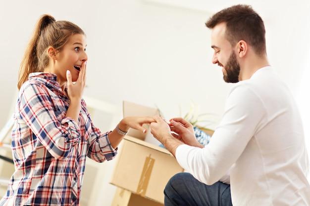 Glückliches erwachsenes paar, das in ihrer neuen wohnung vorschlägt